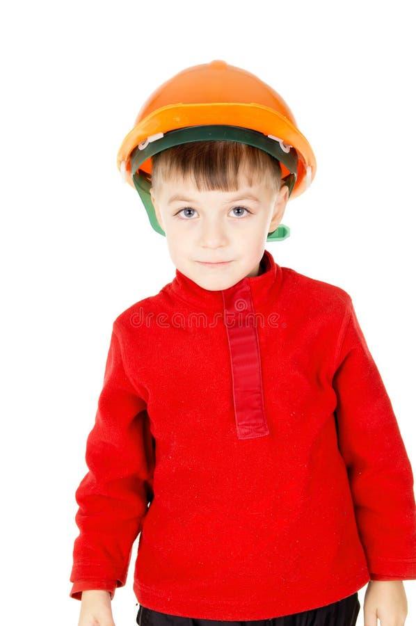 Rapaz pequeno feliz que está com um capacete foto de stock royalty free