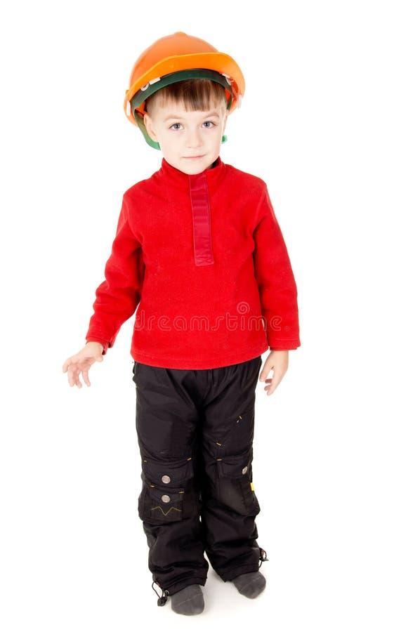 Rapaz pequeno feliz que está com um capacete foto de stock