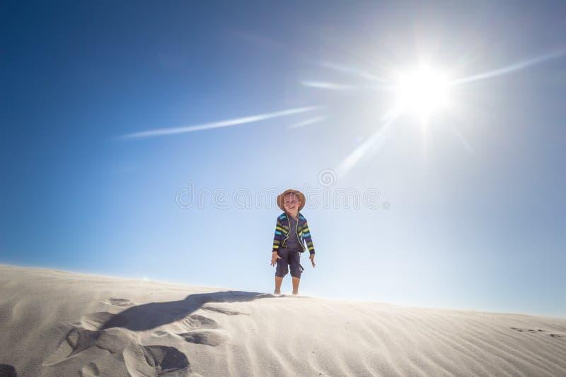 Rapaz pequeno feliz que está no auge da duna de areia ventosa em uma SU atrasada imagens de stock royalty free