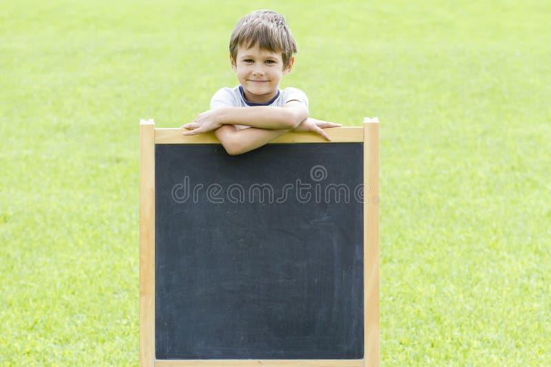 Rapaz pequeno feliz que está no quadro-negro Copie o espaço para o texto foto de stock