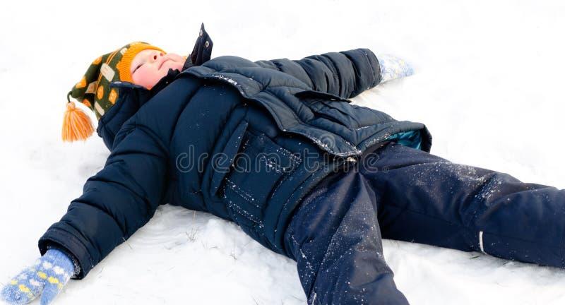 Rapaz pequeno feliz que faz anjos da neve na neve foto de stock royalty free