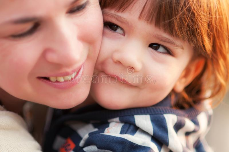Rapaz pequeno feliz que inclina-se maciamente a sua mamã fotografia de stock