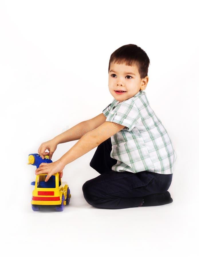 Rapaz pequeno feliz que joga com carros e brinquedos. fotos de stock