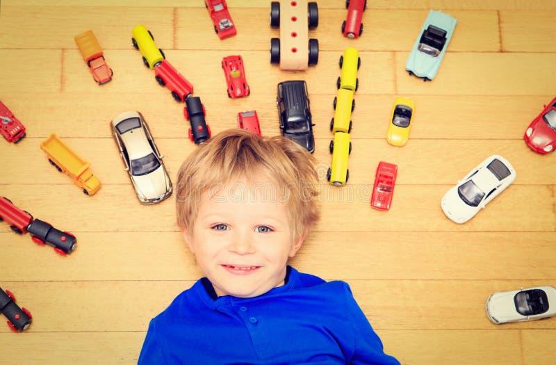 Rapaz pequeno feliz que joga com os carros do brinquedo internos imagem de stock royalty free