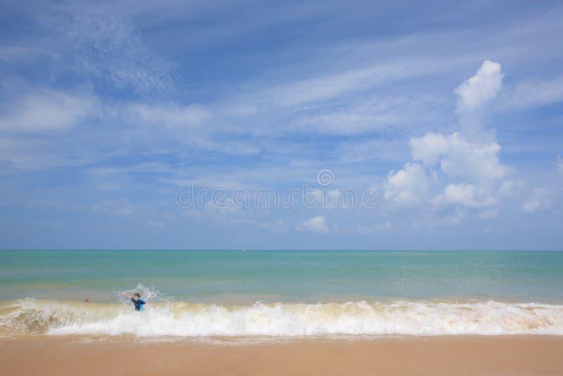 Rapaz pequeno feliz que joga e que surfa no oceano em férias foto de stock royalty free