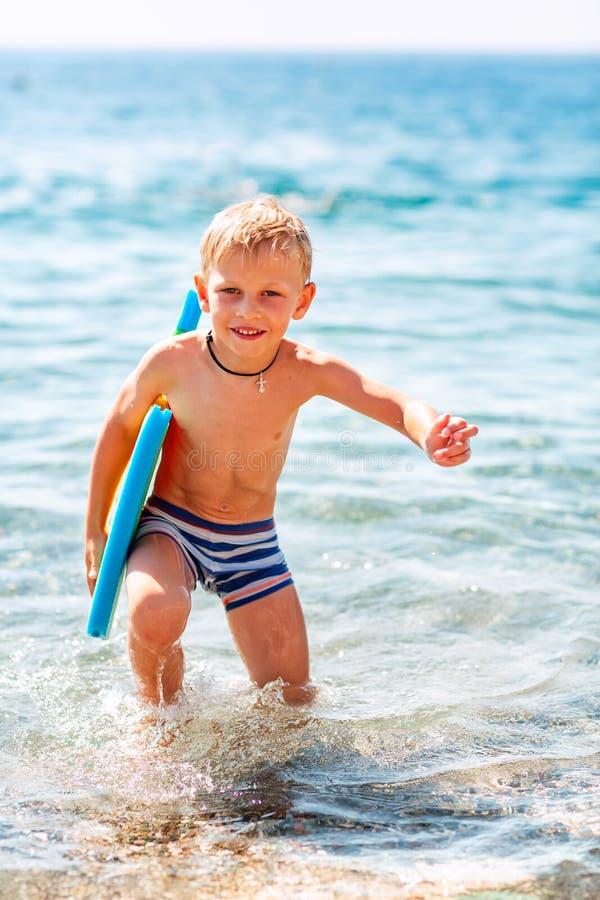 Rapaz pequeno feliz que joga nas ondas no beira-mar imagem de stock