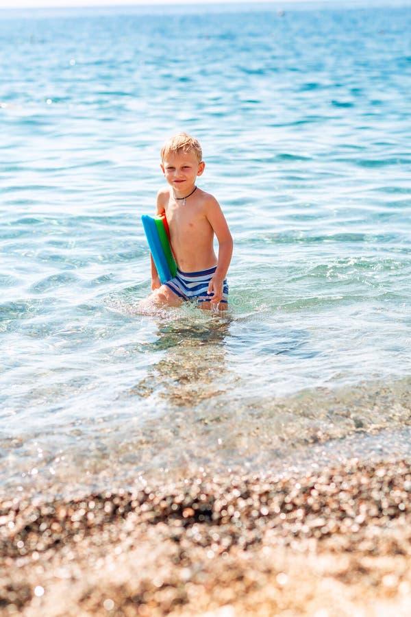 Rapaz pequeno feliz que joga nas ondas no beira-mar fotografia de stock