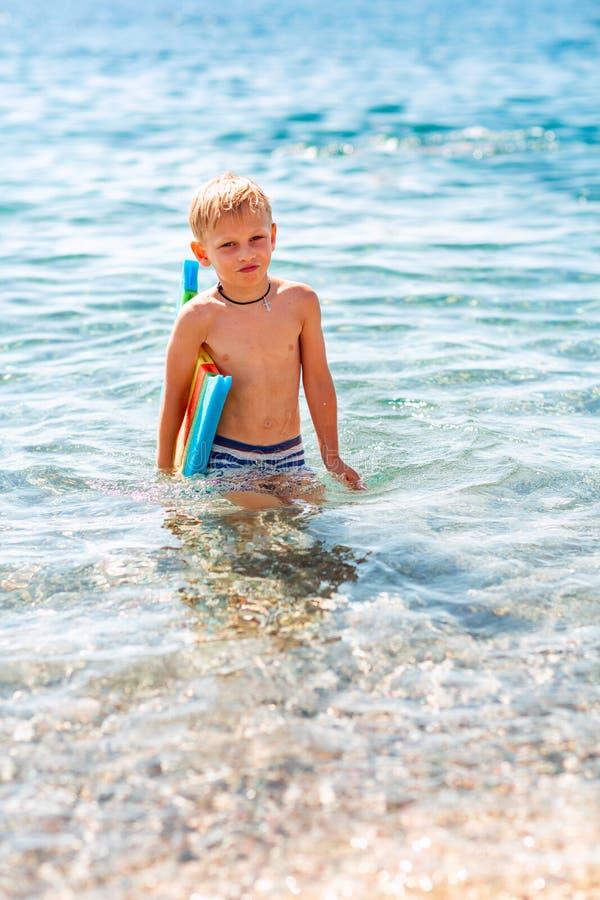 Rapaz pequeno feliz que joga nas ondas no beira-mar imagens de stock royalty free