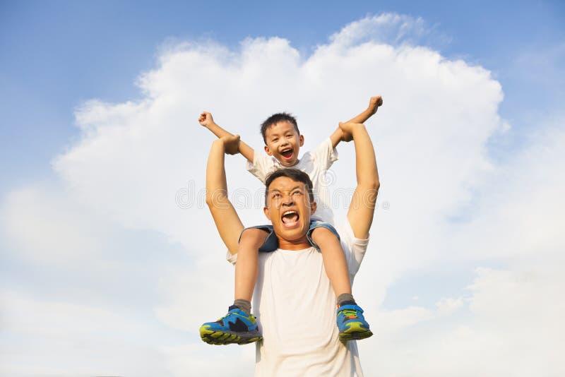 Rapaz pequeno feliz que senta-se no ombro do pai imagens de stock