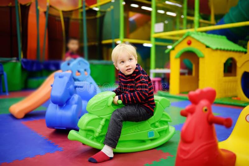 Rapaz pequeno feliz que tem o divertimento com o velomotor plástico do brinquedo-balanço/lupulagem no centro do jogo imagem de stock