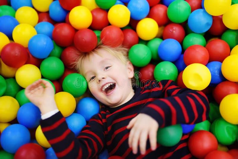 Rapaz pequeno feliz que tem o divertimento no poço da bola com bolas coloridas foto de stock