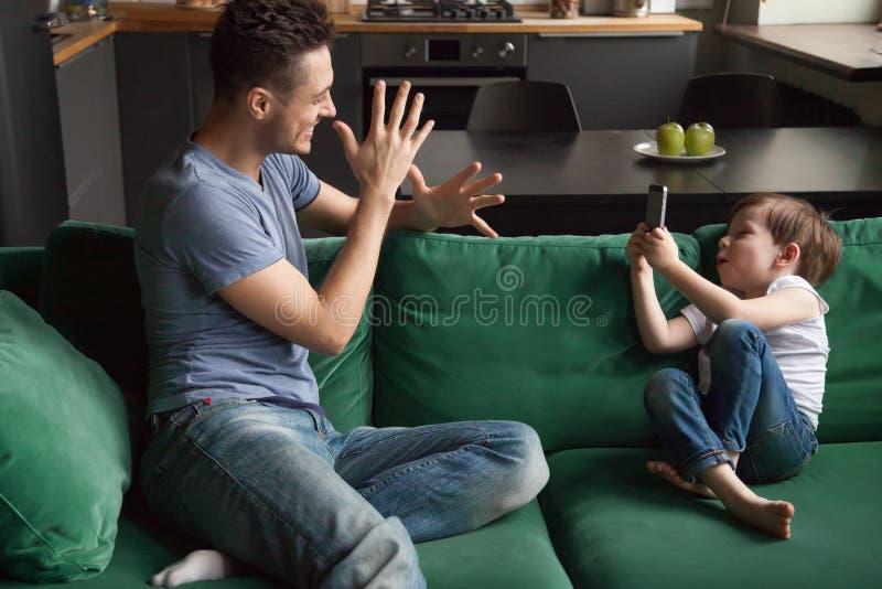 Rapaz pequeno, filho que toma a foto do pai engraçado no telefone foto de stock royalty free