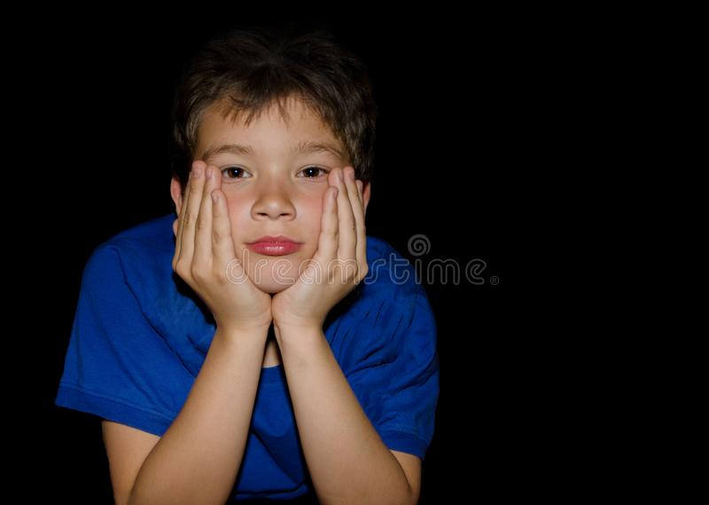 Rapaz pequeno forçado, comprimido, infeliz que guarda sua cabeça sobre o fundo preto imagem de stock