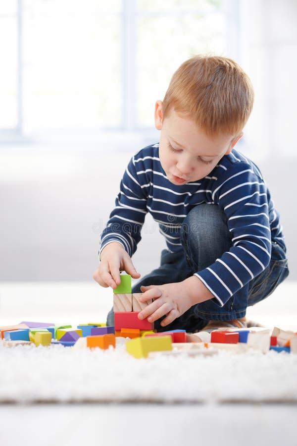 Rapaz pequeno Ginger-haired que joga em casa foto de stock