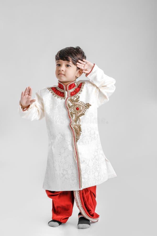 Rapaz pequeno indiano/asiático bonito no desgaste étnico e na bandeira nacional de saudação foto de stock