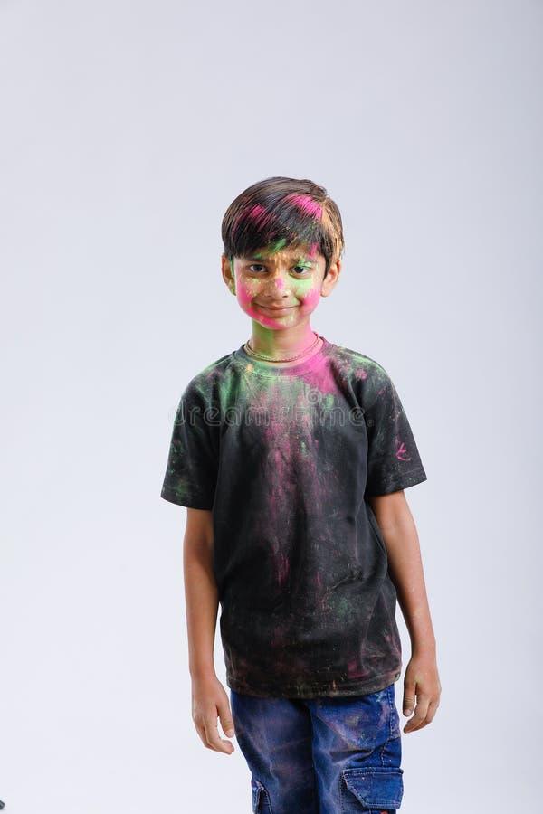 Rapaz pequeno indiano que joga com a cor e que dá expressões múltiplas no festival do holi foto de stock