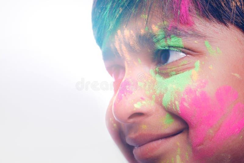Rapaz pequeno indiano que joga com a cor e que dá expressões múltiplas no festival do holi imagem de stock royalty free