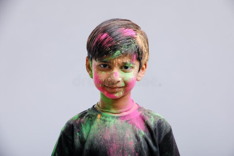 Rapaz pequeno indiano que joga com a cor e que dá expressões múltiplas no festival do holi fotografia de stock