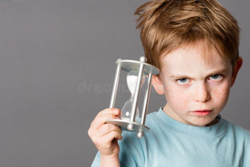 Rapaz pequeno infeliz com um temporizador do ovo para o conceito do tempo foto de stock