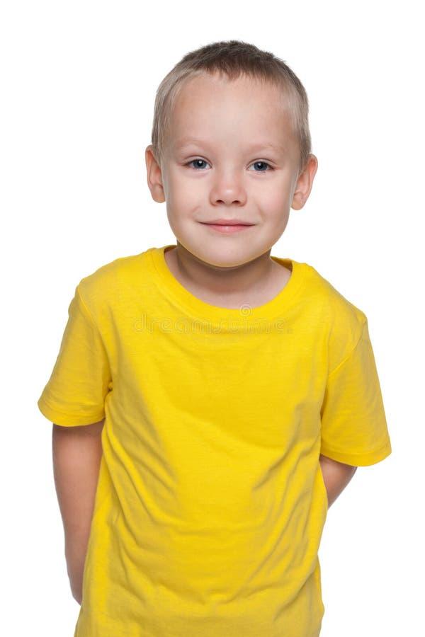 Rapaz pequeno louro em uma camisa amarela fotografia de stock royalty free