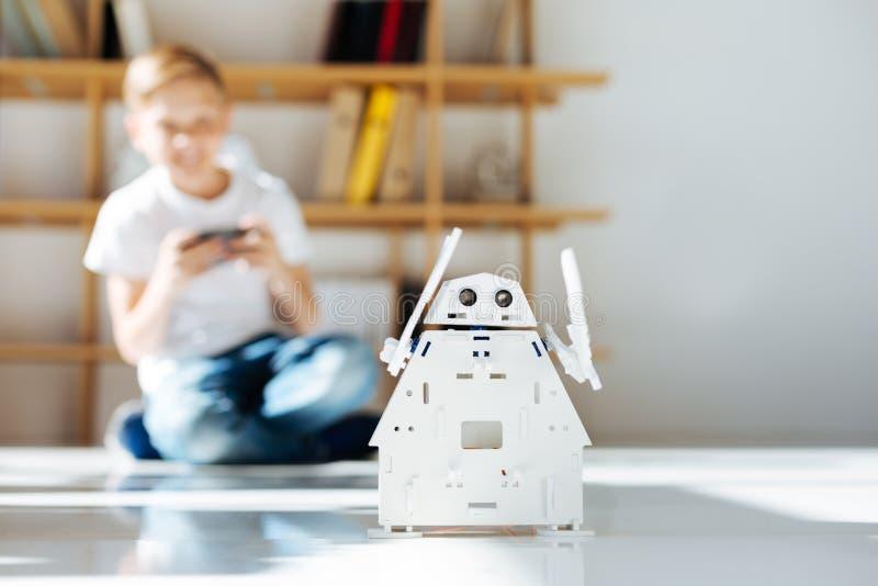 Rapaz pequeno louro que aprecia seu brinquedo novo do robô imagens de stock