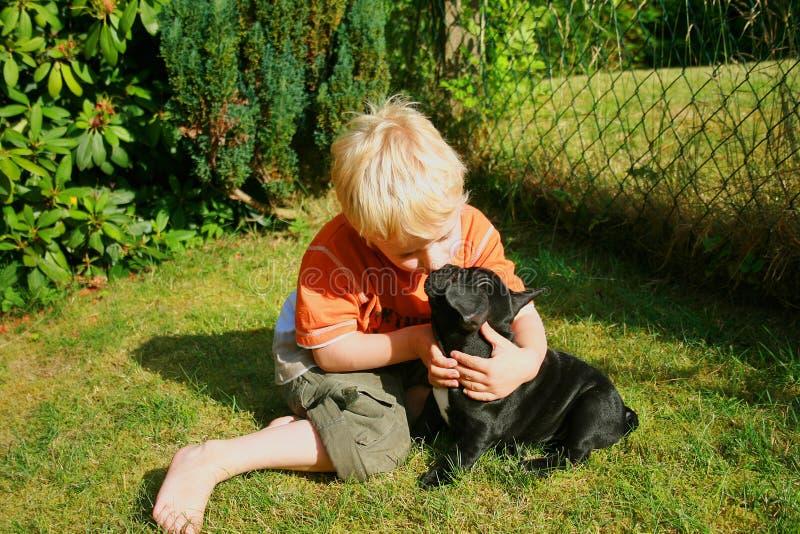 Rapaz pequeno louro que beija o cão fotos de stock