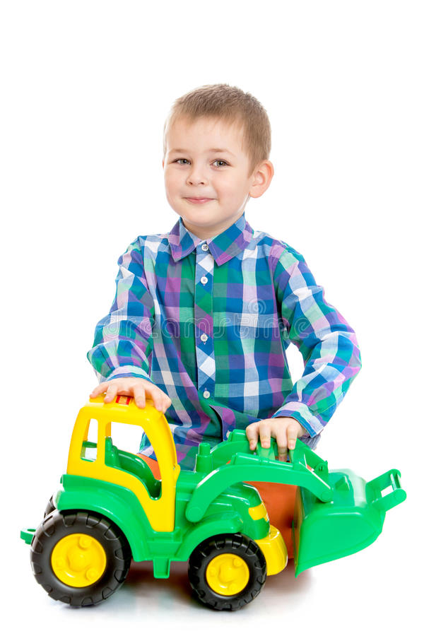 Rapaz pequeno louro que joga com um trator do brinquedo foto de stock