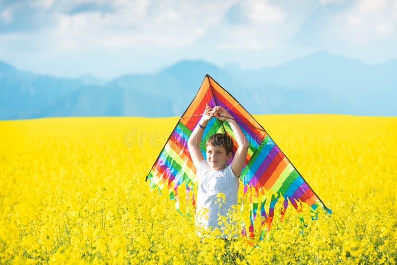 Rapaz pequeno na camisa branca que corre com o papagaio no campo amarelo crescendo fotografia de stock