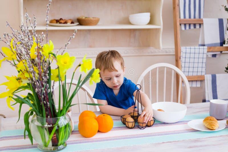 Rapaz pequeno na cozinha Criança que joga com os ovos na cozinha fotografia de stock