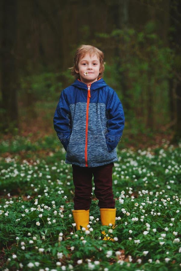 Rapaz pequeno na floresta da mola com muitas flores foto de stock