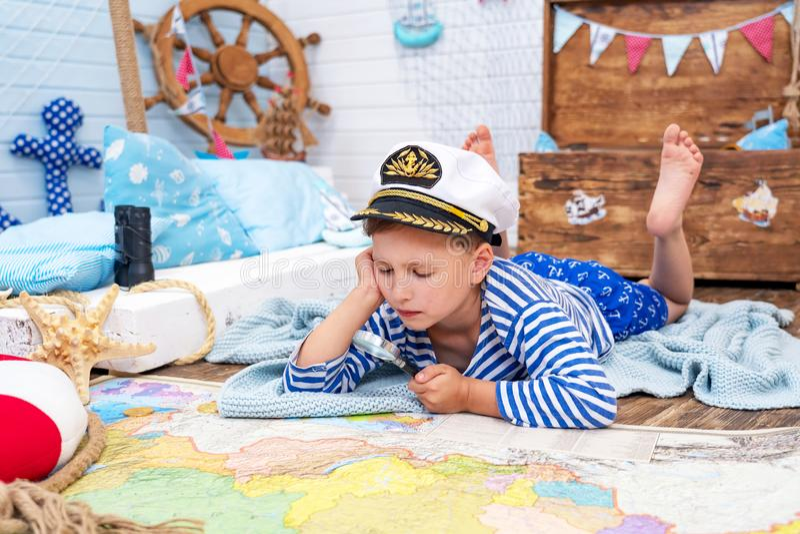 Rapaz pequeno na imagem de um marinheiro que joga em sua sala examina completamente fotografia de stock