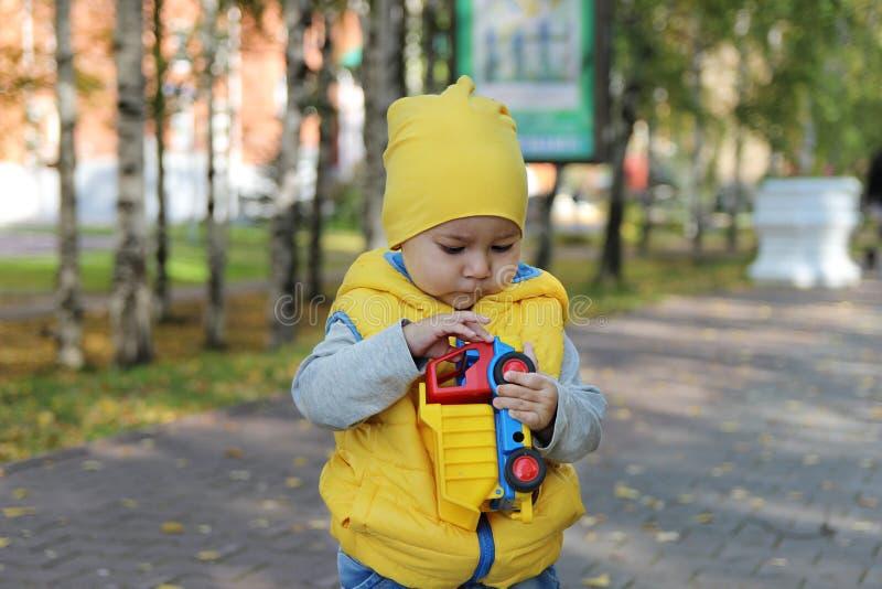 Rapaz pequeno na roupa amarela que realiza em suas mãos um caminhão do brinquedo foto de stock royalty free