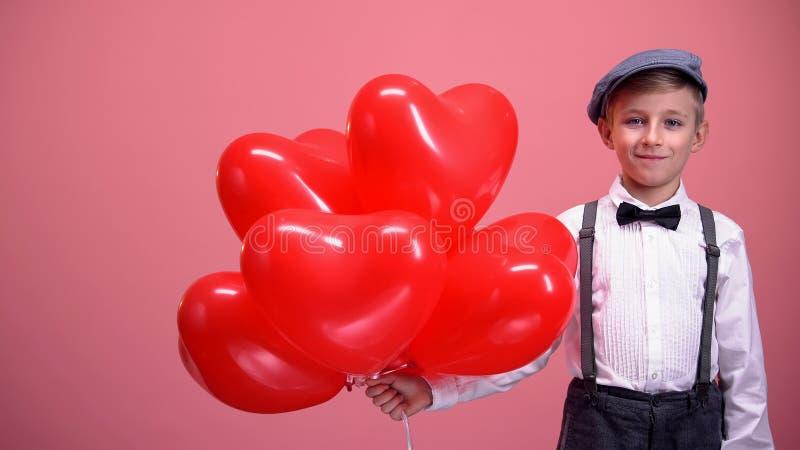 Rapaz pequeno na roupa do vintage com balões coração-dados forma que sorri, dia de Valentim imagens de stock royalty free