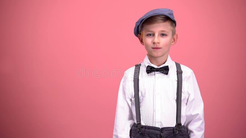 Rapaz pequeno na roupa do vintage que olha na câmera, isolada no fundo cor-de-rosa imagem de stock