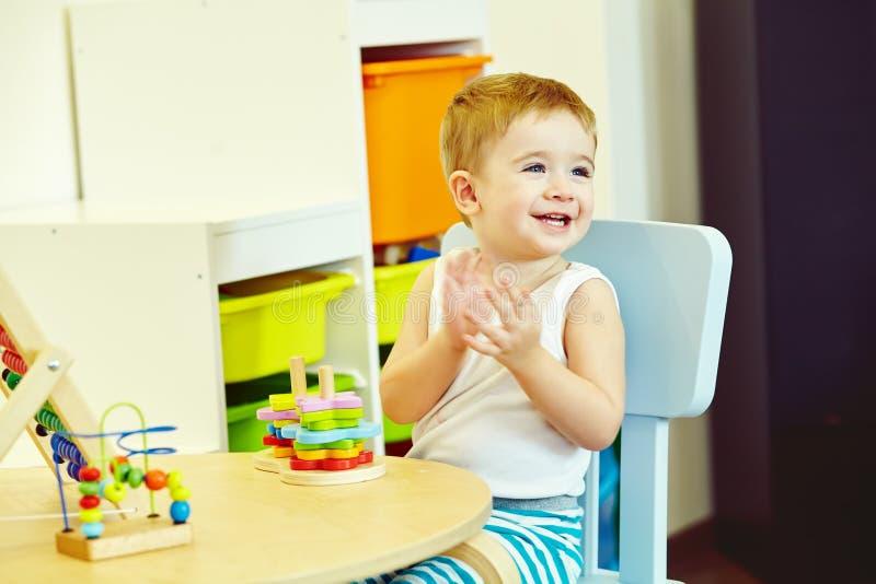 Rapaz pequeno na tabela que joga no jogo tornando-se foto de stock