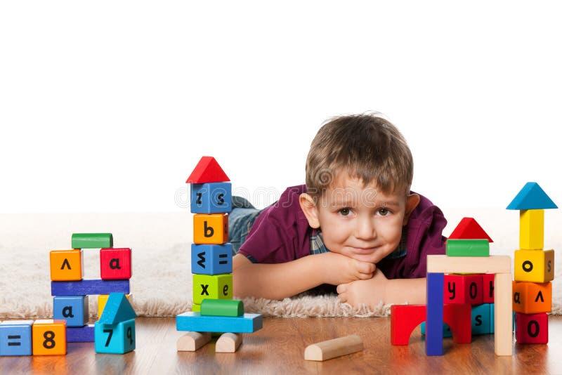Rapaz pequeno no assoalho perto dos brinquedos imagem de stock