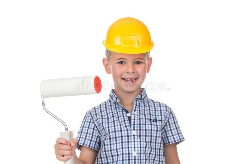 Rapaz pequeno no capacete amarelo e na camisa quadriculado que jogam um pintor Ocupações diferentes Isolado sobre o branco fotografia de stock royalty free