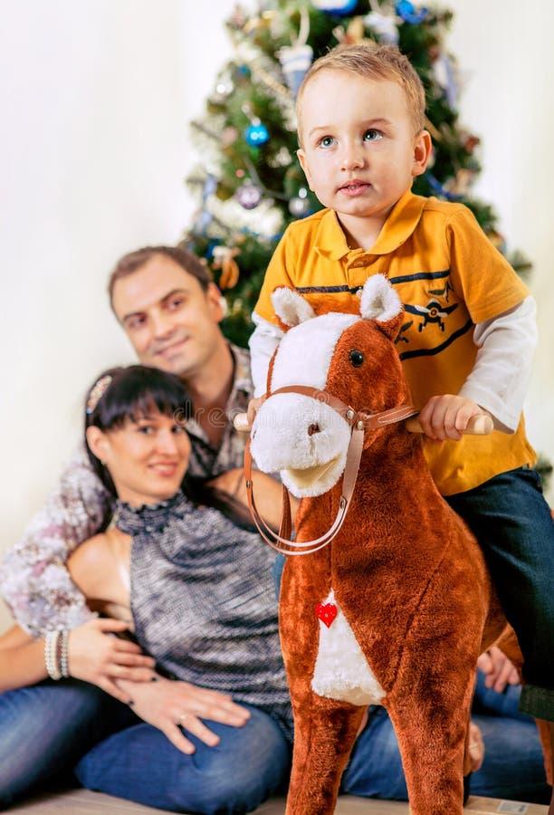 Rapaz pequeno no cavalo do brinquedo com seus pais sob a árvore de Chrismas fotografia de stock