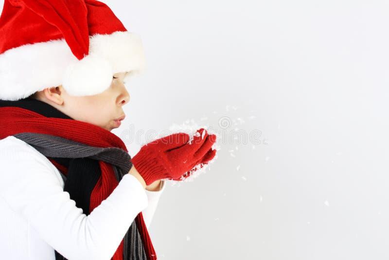 Rapaz pequeno no chapéu e o lenço de Papai Noel e luvas que fundem flocos de neve imagens de stock