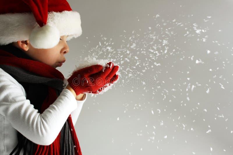 Rapaz pequeno no chapéu e o lenço de Papai Noel e luvas que fundem flocos de neve fotos de stock