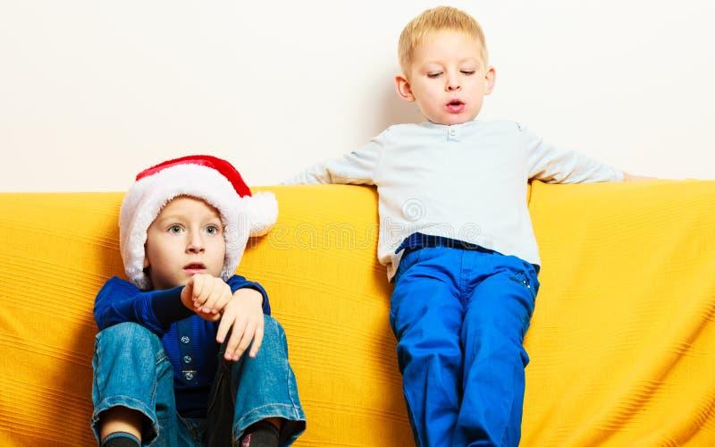Rapaz pequeno no chapéu vermelho de Santa com seu irmão em casa fotografia de stock royalty free