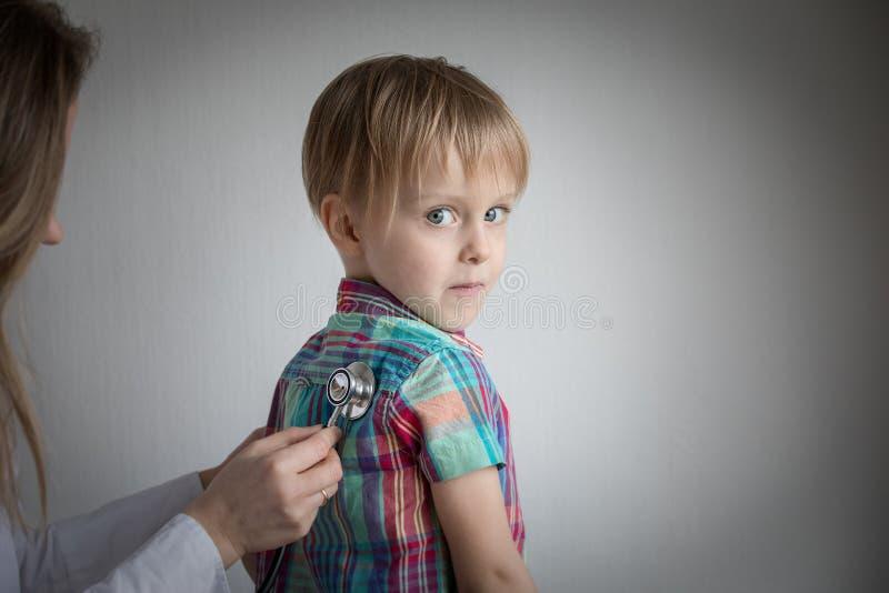 Rapaz pequeno no doutor, estetoscópio de utilização fêmea imagem de stock