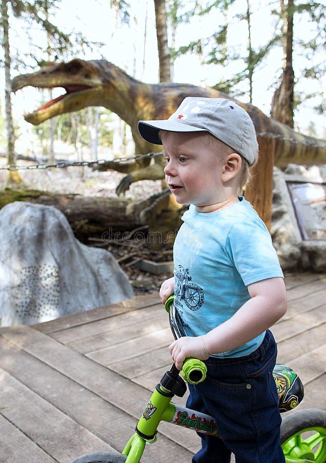 Rapaz pequeno no fundo dos sinais com a descrição de um dinossauro no parque dos dinossauros fotos de stock royalty free