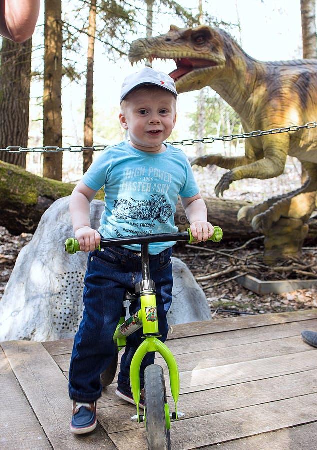 Rapaz pequeno no fundo dos sinais com a descrição de um dinossauro no parque dos dinossauros foto de stock