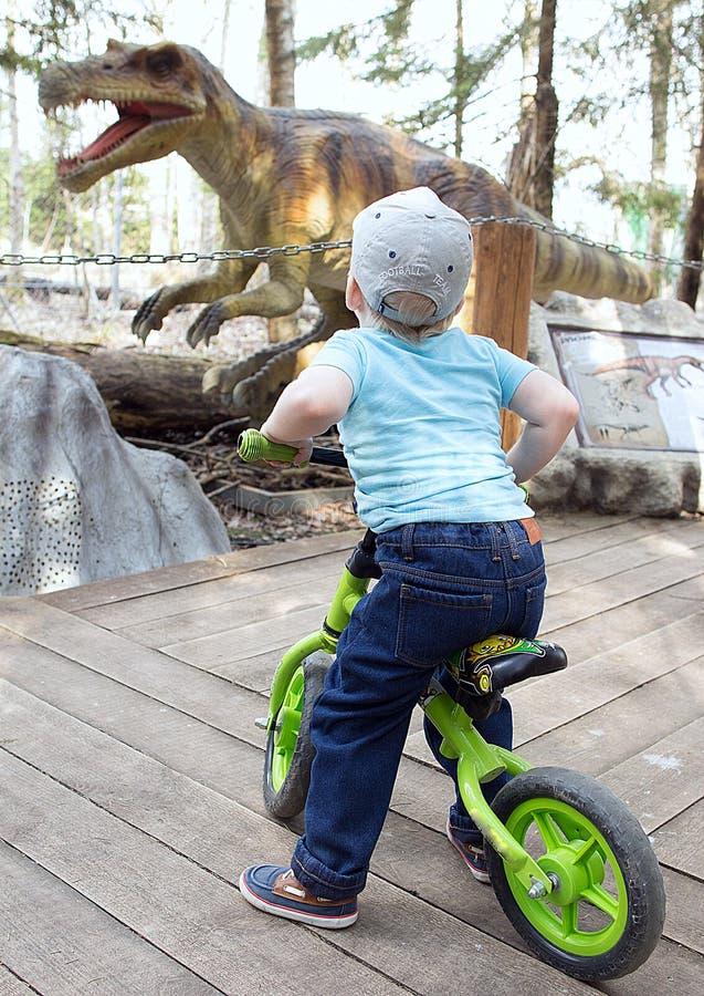 Rapaz pequeno no fundo dos sinais com a descrição de um dinossauro no parque dos dinossauros imagens de stock royalty free