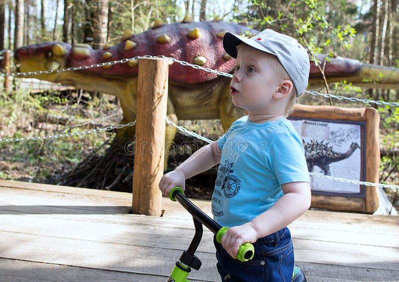Rapaz pequeno no fundo dos sinais com a descrição de um dinossauro no parque dos dinossauros imagem de stock
