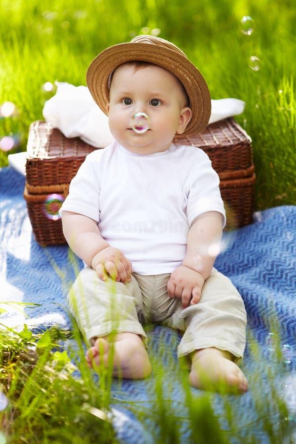Rapaz pequeno no jardim. Piquenique. fotos de stock