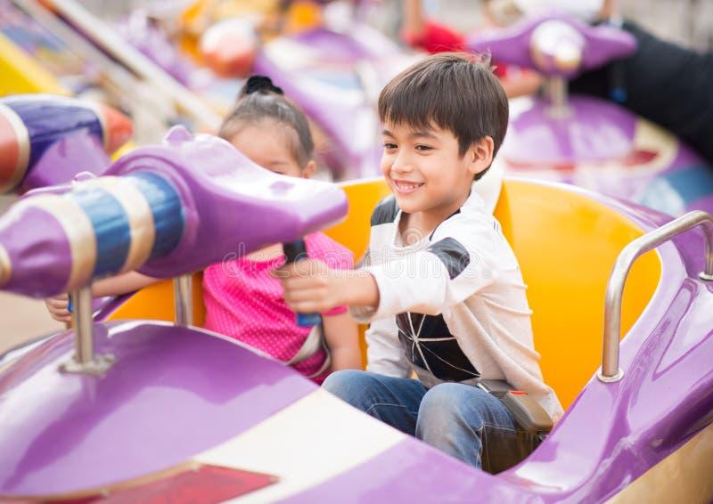 Rapaz pequeno no parque de diversões exterior imagem de stock