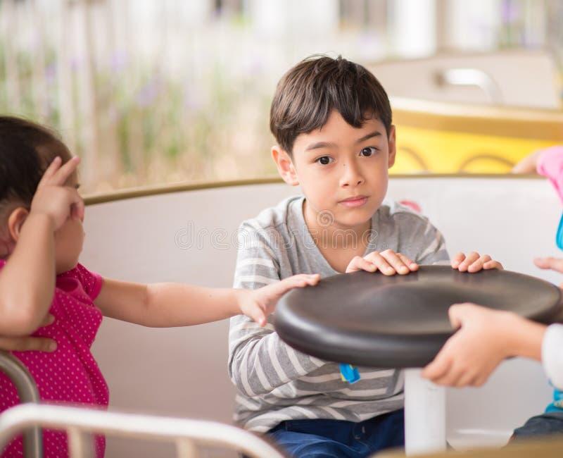 Rapaz pequeno no parque de diversões exterior foto de stock