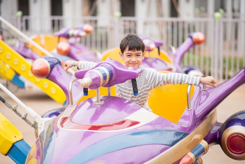 Rapaz pequeno no parque de diversões exterior imagens de stock